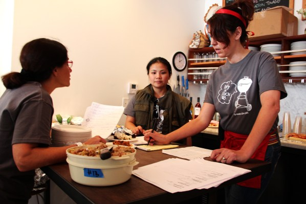 Mary Ladd (right) tallies the results from the pie contest. She helped organize the event, and she sported a red headband with a large lattice-crust pie fascinator angled to the right. Photo by Jessica Naudziunas.