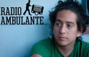 A photo of Daniel Alarcón, the executive producer of Radio Ambulante. Here he sits next to a blue wall, looking pensive.