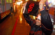 "Raylene Lopez, age 19, of Bayshore, shows her Giants pride by cheering on passing cars along Mission Street. ""Everytime the Giants win my brother and I come to the Mission to celebrate because this is where it's at,"" said Lopez."