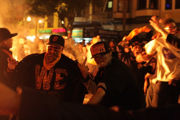 Giants fans pose for a photo in front of a bonfire on 22nd and Mission streets on Sunday. Photo by Rigoberto Hernandez