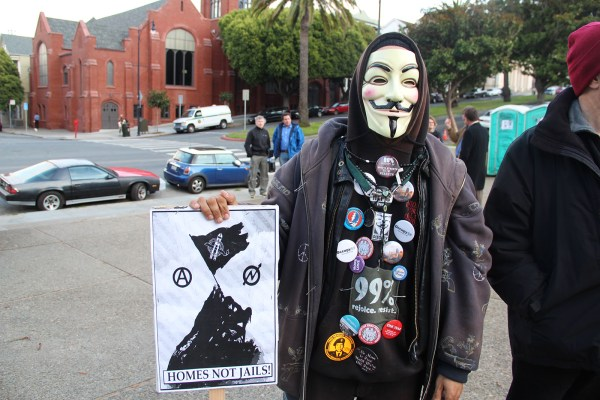 A masked protester waits at Dolores Park before a rally and march in support of World Homeless Action Day. Photo by Carly Nairn.