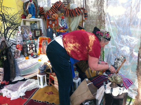 Mixed media artist Nancy Ann Statler creates an altar to honor those she's lost with help from her friends Sugar Skull Productions, who will be performing at the park at 9 p.m.