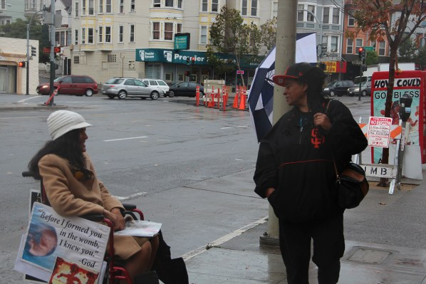 A woman stops to read the signs and talk to anti-abortion activist Erika Hathaway. Photo by Carly Nairn.