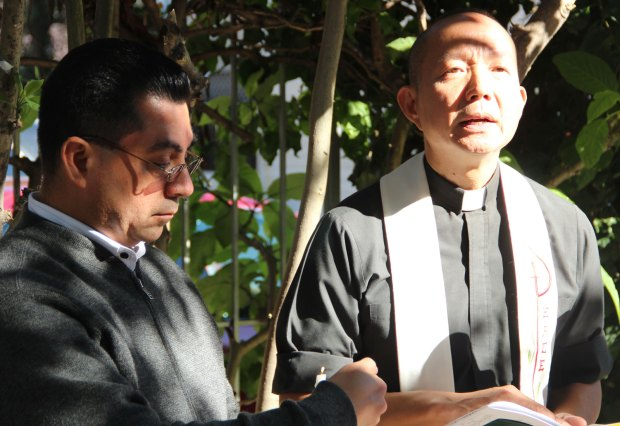 Father Daniel Nascimento (right) and Julio Escobar, Coordinator of Restorative Justice Programs for the Archdiocese of San Francisco pray at a memorial service for homicide victim Jose Matias-Aguilon on Monday, November 5.