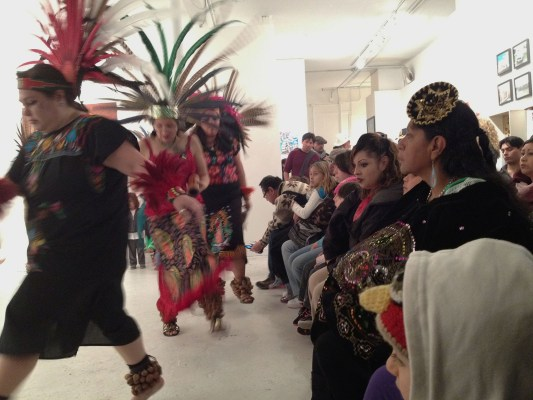 A crowd inside Galeria de la Raza watches a traditional Mayan dance.