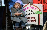A child listens to tenants speak at a protest against the Ellis Act.