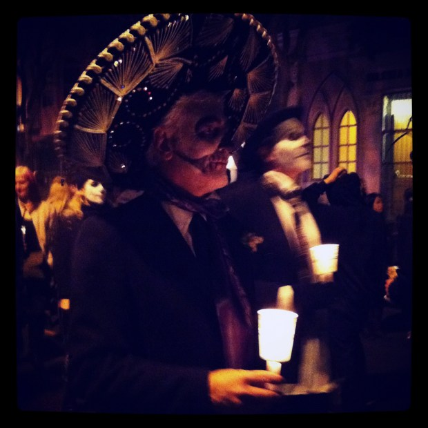 People with skulls painted on their faces walk in the Dia De Los Muertos Procession.