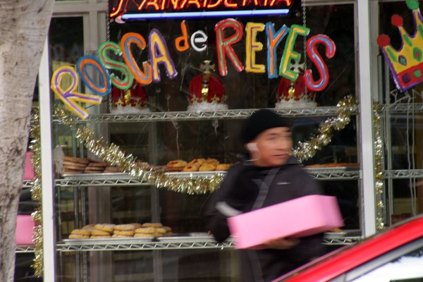 A man carries a Rosca De Rey outside Panaderia La Mexicana.