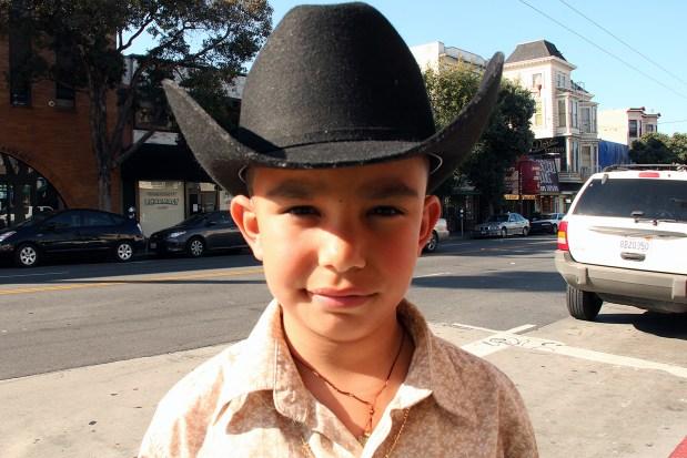 A little boy wears a cowboy hat on Mission Street.