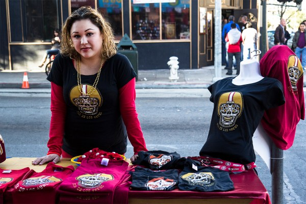 Ana Manzanares from Mixcoatl Arts and Crafts sells 49ers gear in front of the store. Her co-worker Connie Rivera said that the day was excellent for promoting small businesses. (Photo by Marta Franco)