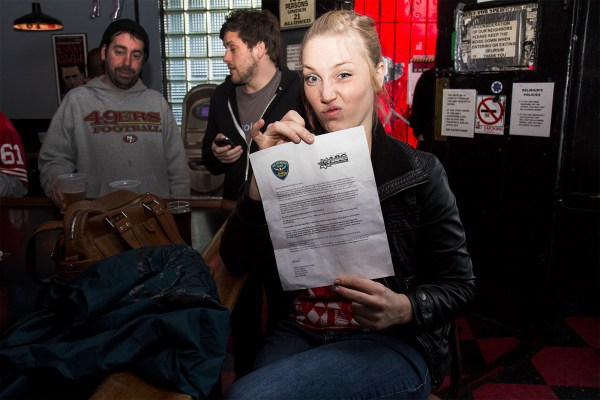 Leslie Hicks, who works at The Hideout at Dalva, displays a letter that the SFPD Mission Station mailed to businesses in hopes of promoting safety during the game. Hicks was watching the game at Delirium before starting her shift. (Photo by Marta Franco)