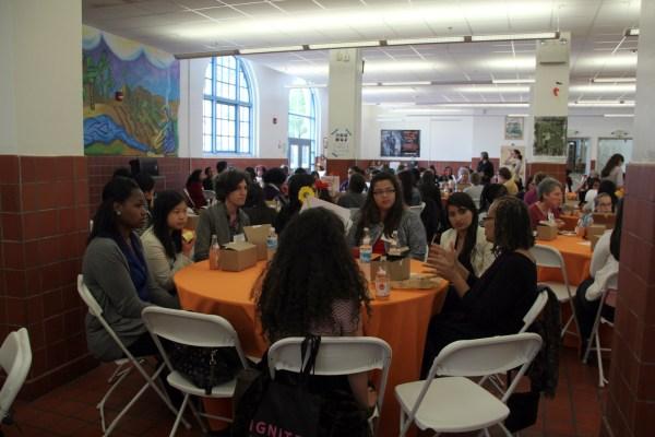 jóvenes mujeres y políticos locales se reúnen para almorzar.
