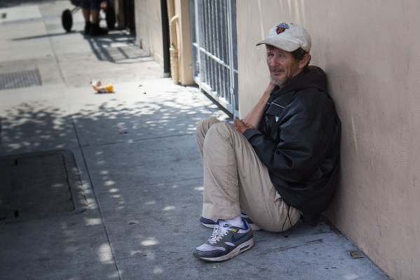 A man sits on the ground on Capp St.
