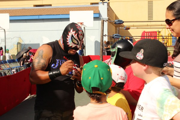 Fans eagerly lined up for Lucha Libre wrestler autographs. Photo by Heather Mack.