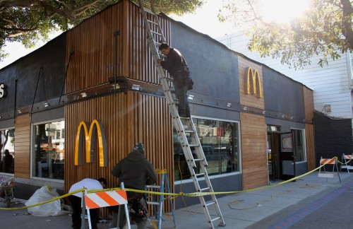 Workers put finishing touches on the exterior of revamped McDonald's on 24th and Mission streets.