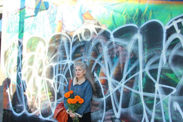 Muralist Juana Alicia in front of her marred mural. Photos by Greta Mart.