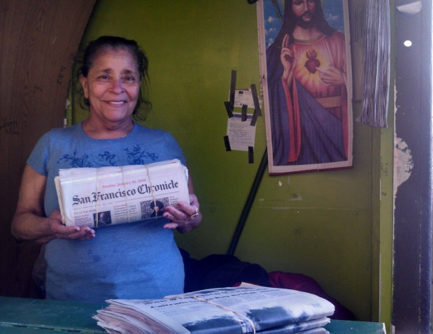 Rosa Campos displays a newspaper in front of the stand. Photo by Erica Hellerstein.