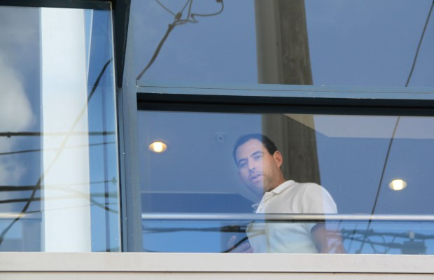 A man inside Vanguard Properties looks down on the crowd during the protest.