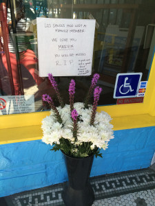 """""""Los Shucos has lost a family member. We love you Marvin. You will be missed. R.I.P. A great cook and a great friend. He loved to dance and drink Rockstar!"""", reads the sign outside the Shucos window, with flowers set up."""