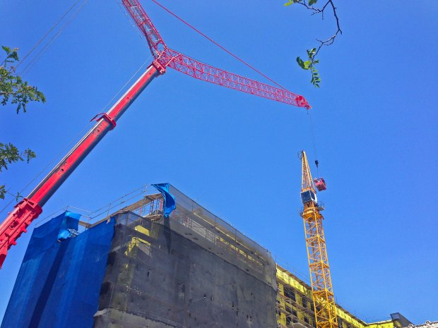 Construction Crane lifts workers to remove existing structure.