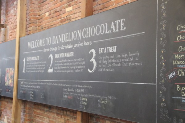 The store's chalkboard sign describes Dandelion Chocolate's model and shows offerings of its classes and tours. Photo by Joe Rivano Barros.