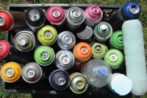 A box of used spray paint cans lies in the grass at the annual Urban Arts Festival in the Mission District. Photo by Leslie Nguyen-Okwu.
