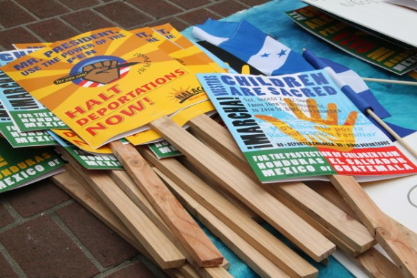 Dozens of signs and Central American flags were left over from the protest. Photo by Joe Rivano Barros.