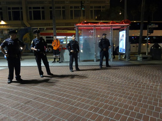 Nearly a dozen police officers stood around the perimeter of the 24th STreet BART Plaza. Photo by Lydia Chávez