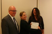 The Community Land Trust's Richard Hurlburt and Director Tracy Parent present the down payment check for the Pigeon Palace with Carin McKay