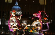 Papier-mache skeletons and fantastical creatures called alebrijes dance at Davies Symphony Hall with City Hall in the background.