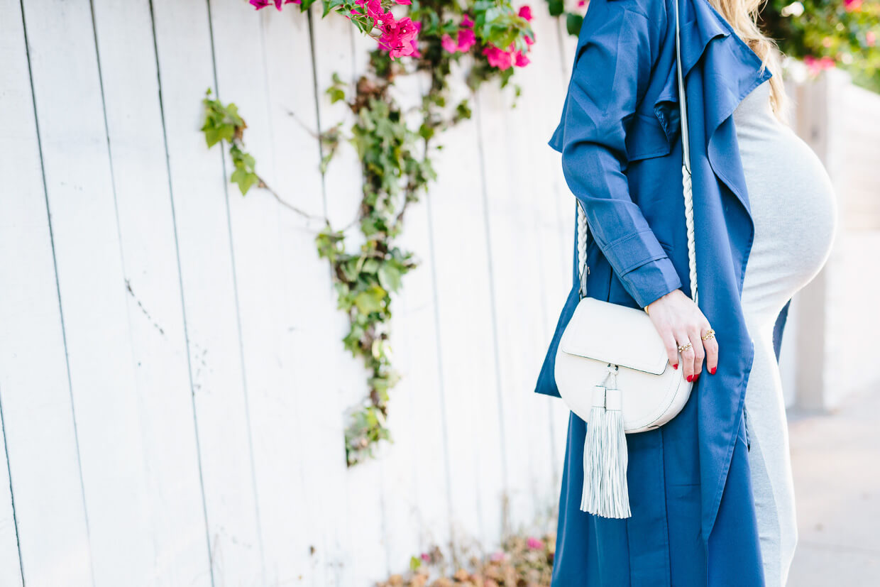 dress the bump in a blue trench coat and scoop neck dress