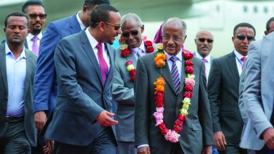 Eritrea's Foreign Minister Osman Sale, center right, is welcomed by Ethiopia's Prime Minister Abiy Ahmed, center left, upon the Eritrean delegation's arrival at the airport in Addis Ababa, Ethiopia Tuesday, June 26, 2018. The delegation of top officials from Eritrea arrived Tuesday in Ethiopia for the first peace talks in 20 years and were welcomed at the airport by Ethiopian Prime Minister Abiy Ahmed, signifying the importance of their visit. (AP Photo/Mulugeta Ayene)