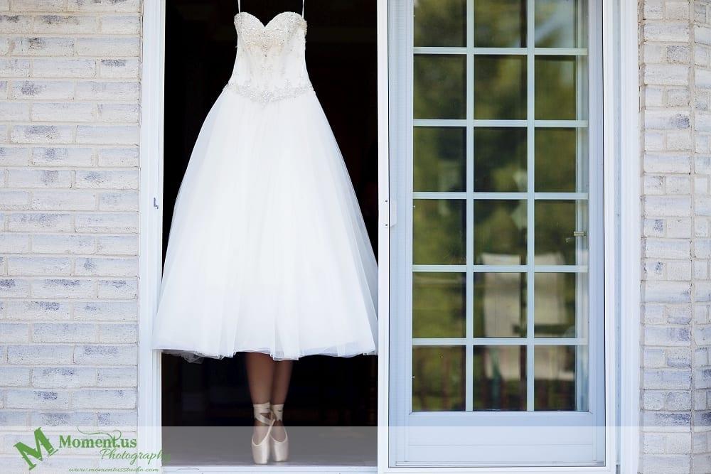elegant Cornwall wedding - wedding dress hanging in doorway pointe shoes underneath