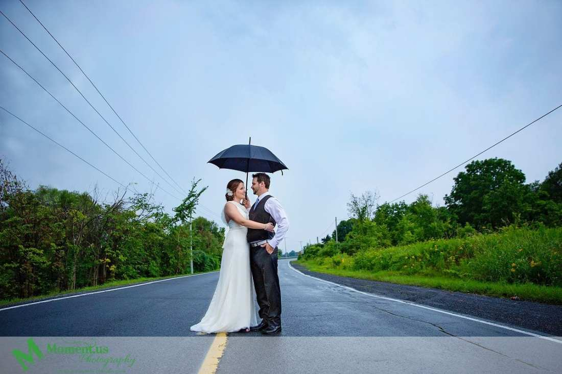 Cornwall weddings - Couple standing on road with umbrella