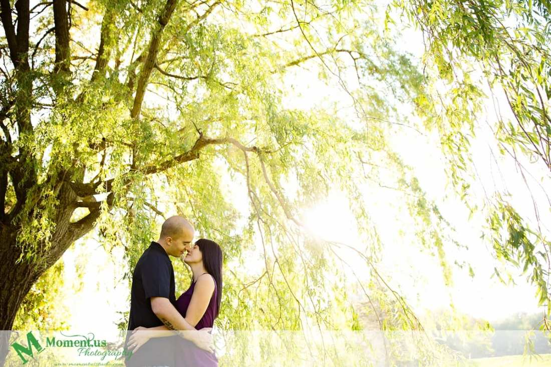 Cornwall engagement photographer - man and woman kissing under willow tree