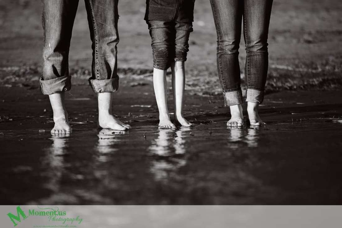 Cornwall engagement photographer - three pairs of legs in water