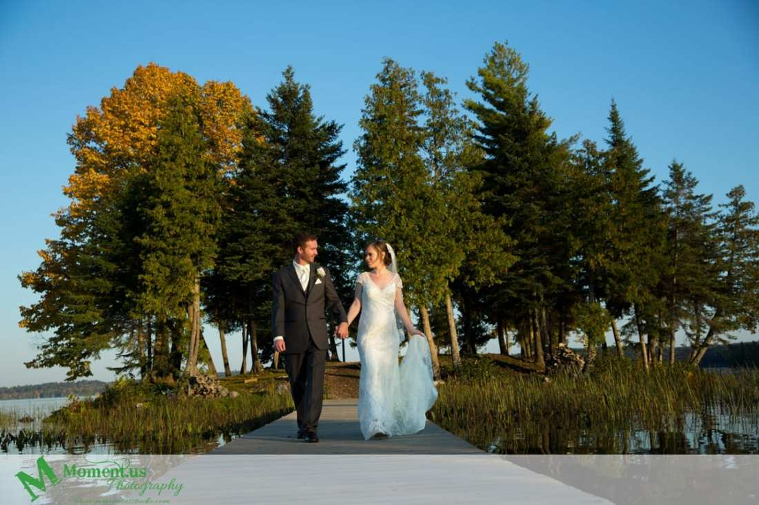 bride and groom walking across wooden bridge - Calabogie Peaks Wedding