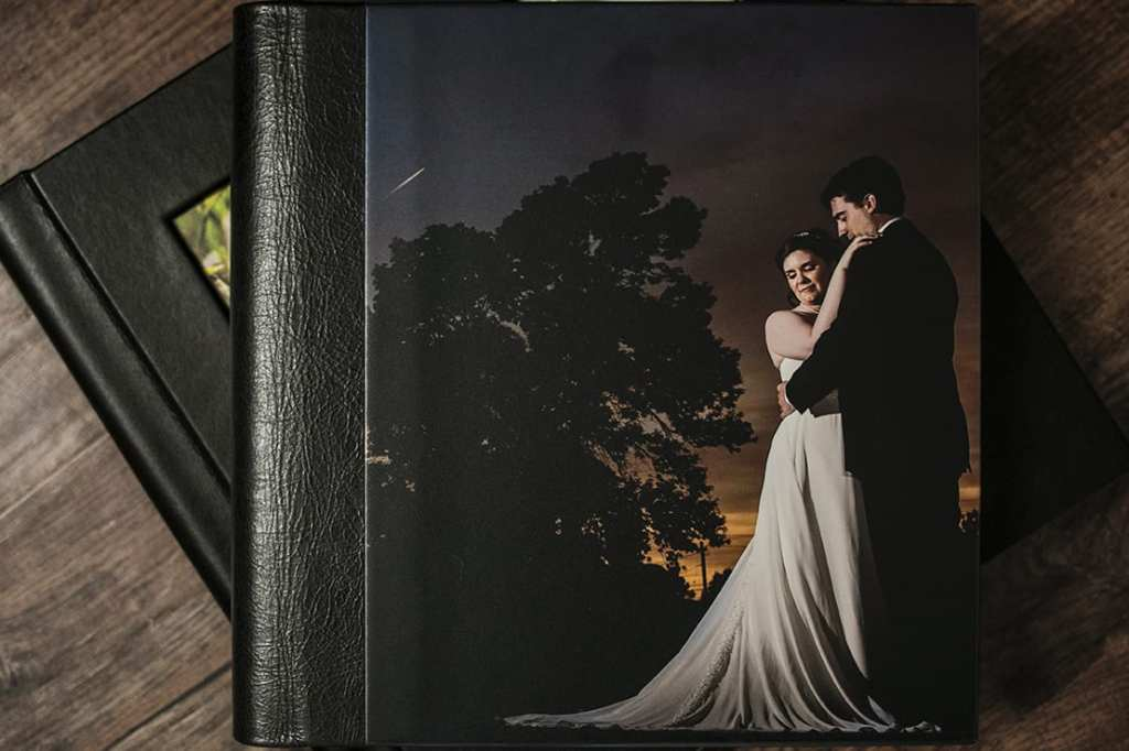 cover of Modern Ontario Wedding Album featuring couple cuddling at sunset with tree shadowed in background