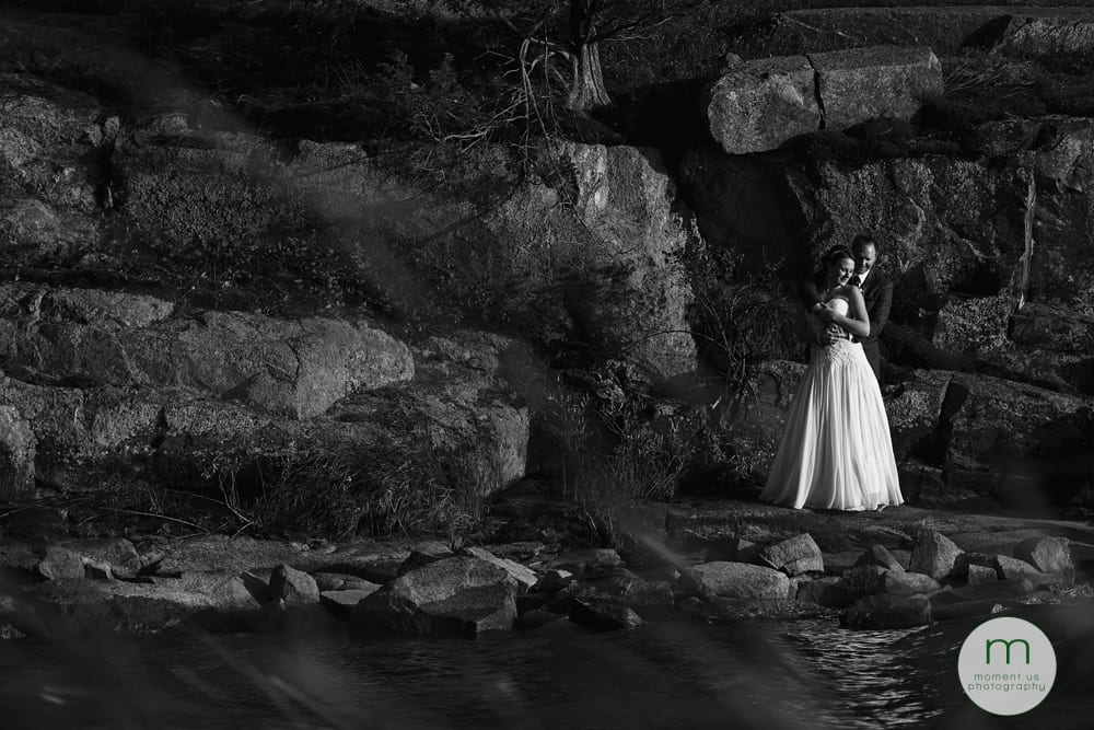 bride and groom on rocky outcrop in bay
