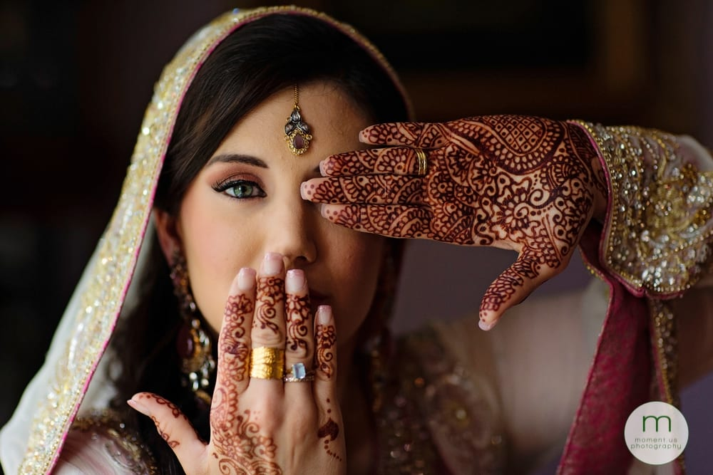bride with mehndi hands by face