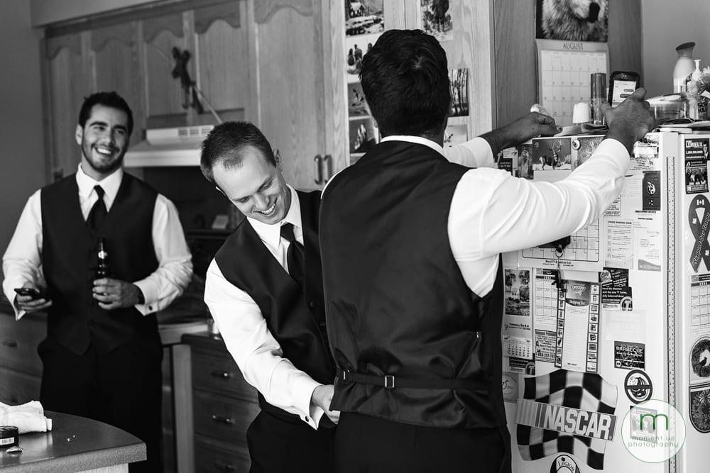 groomsman pinning groom's vest