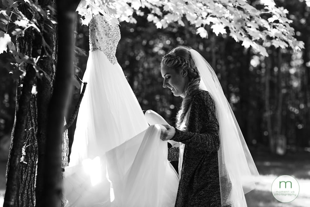 bride adjusting dress in forest