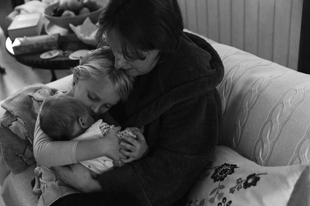 Stockholm mom cuddling with two daughters
