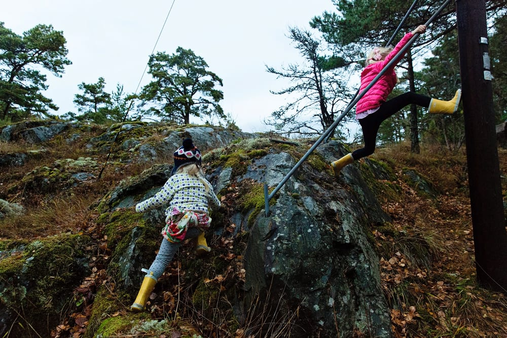 Stockholm sisters playing on rocks and poles