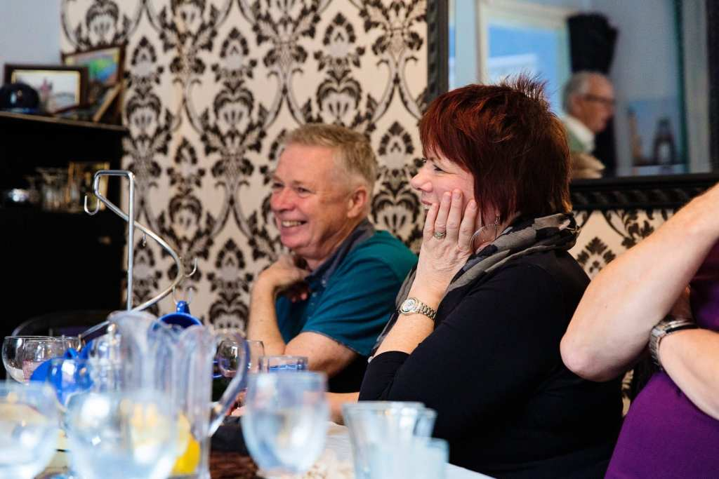 Husband and wife laughing during Manchester family lunch