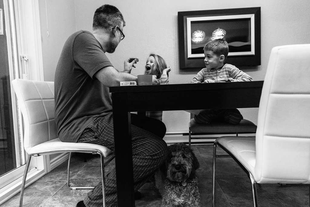 portrait of dad with children and dog at breakfast table