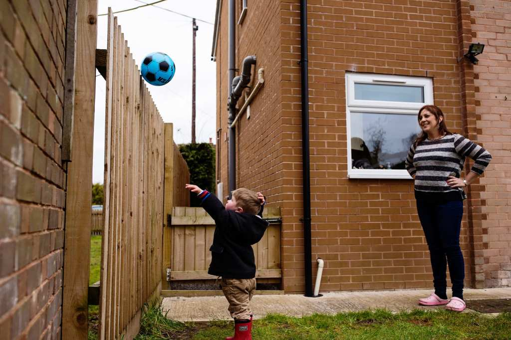 boy throwing ball over wall during South Wales family session