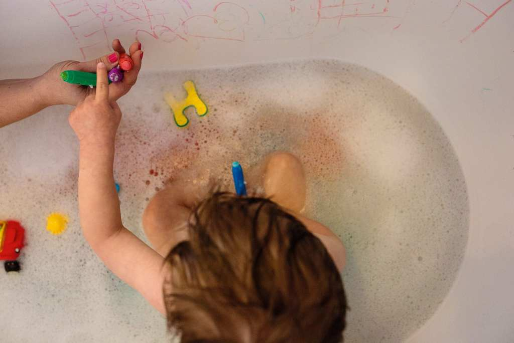 boy playing with bath crayons