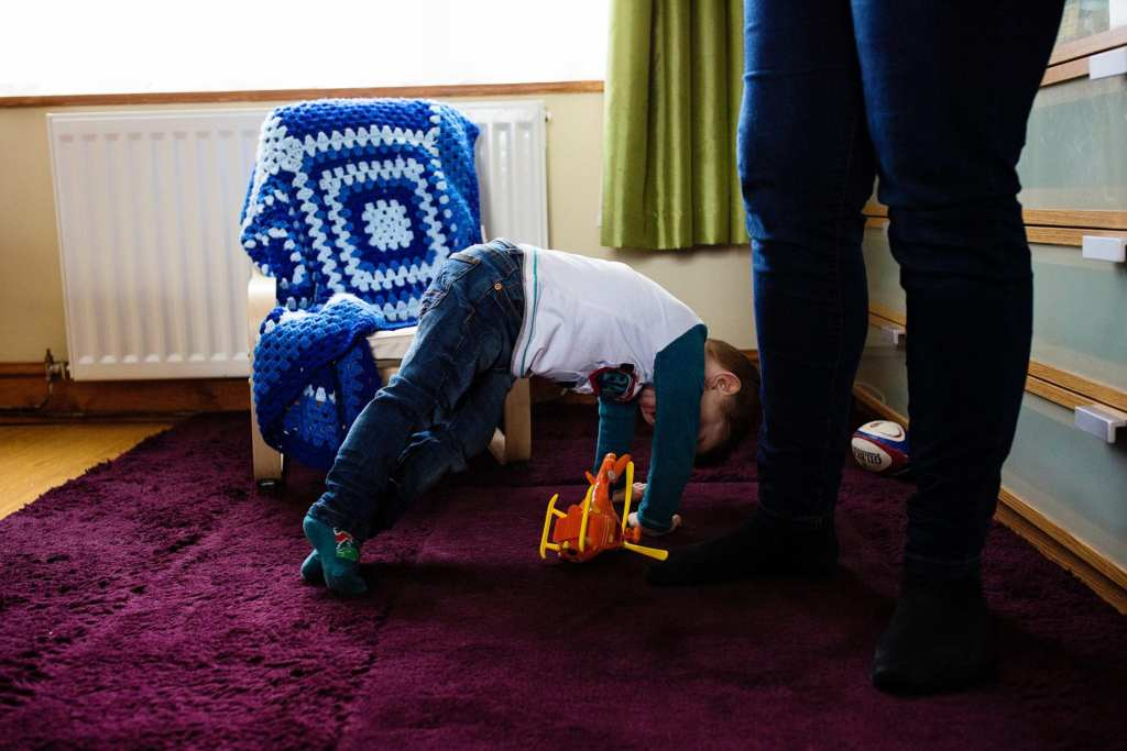 boy playing toys on floor during South Wales family photo session