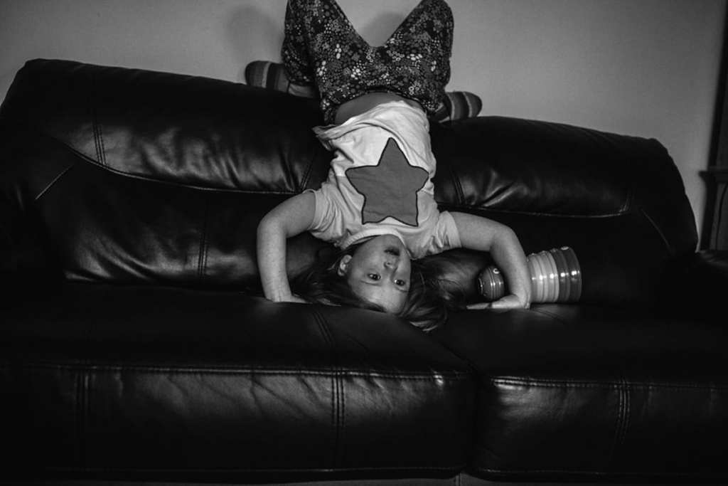 girl standing on head on the couch